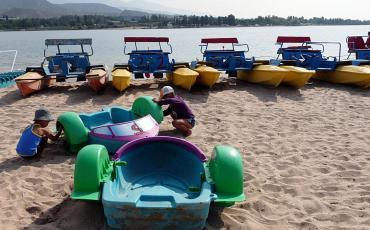 White sand beach with boats at lake Issyk-Kul