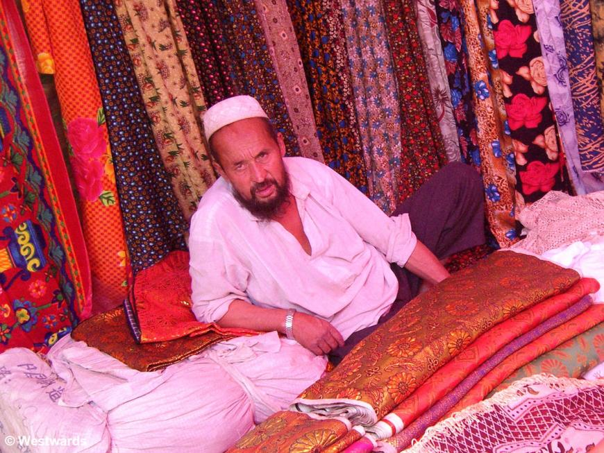 Uighur vendor leaning on bales of colourful cloth