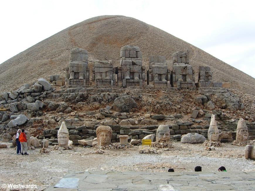 Natascha and another independent traveller standing between huge torsos and heads of ancient gods on the Eastern terrace of Nemrud Dagi