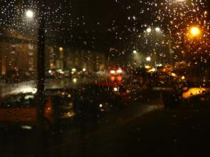 Glowing nightscape through wet window.
