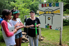 Maddie and Olivia Bohler, who put together the key of hopes for participants in Saturday's Day of Hope, talk about the placement and meaning behind the lighthouse, which was lit at We Survive's Haven of Hope in Bloomfield.