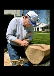After sawing a log in half, bowl maker Wes Kolkmeier, 63, of St. Louis determines the center of the bowl-to-be then nails an angle ruler to the center which enables him to draw a circle on the log. He will then use a chain saw to cut away excess wood around the circle.