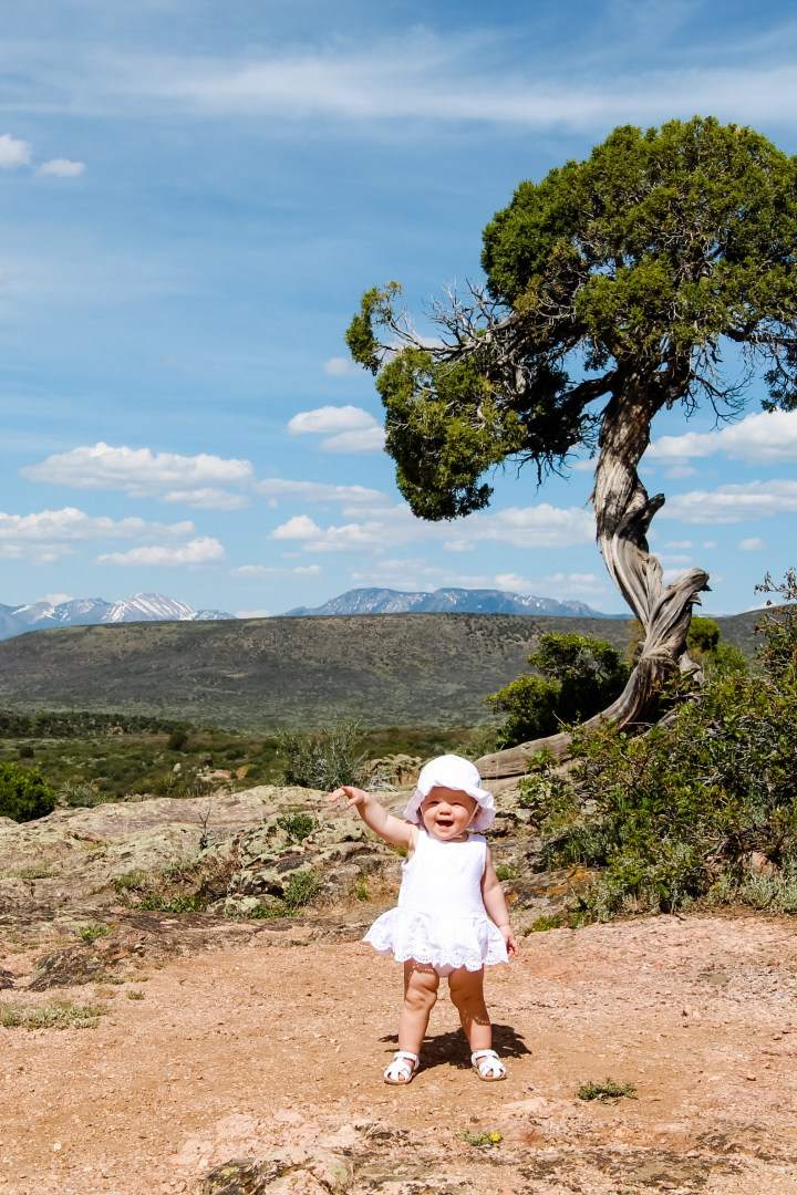 Baby at Black Canyon of the Gunnison National Forest, pointing and smiling, with Juniper tree and mountains in the background, Colorado