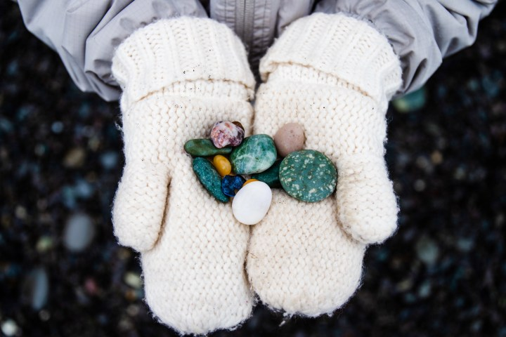 Child's mitten hands holding beautiful, colorful beach rocks on Rialto Beach.