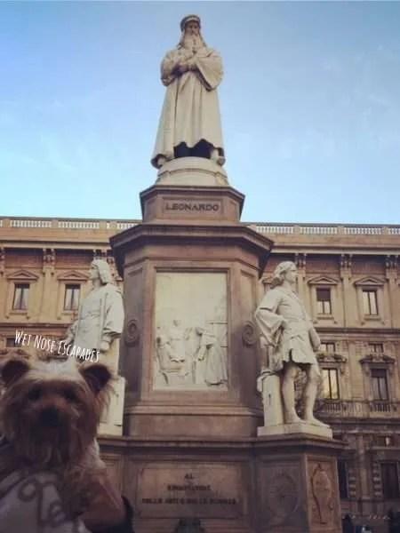 Yorkie dog at Leonardo da Vinci statue in Milan Italy