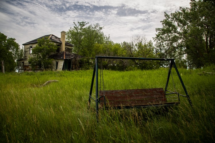 A swing and crumbling house in the abandoned Manitoba ghost town of Ste. Elizabeth.
