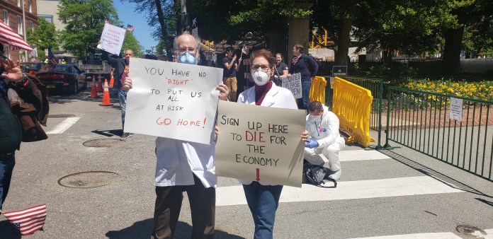 Dr. Erich Bruhn and an unnamed nurse hold signs up as some of the few counter-protesters. Photo by Chip Lauterbach, Capital News Service.