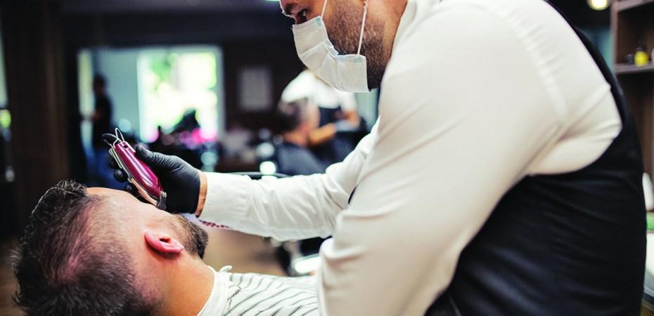 A barber in a mask trims a customer's beard.