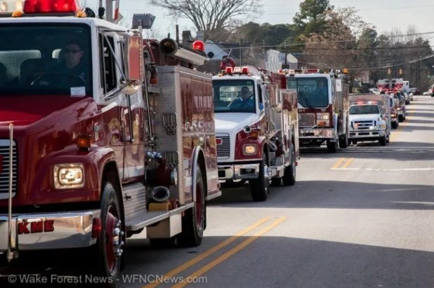 Fire department trucks proceed the remains of fallen firefighter Jeff Fields through Youngsville, NC on December 28, 2013.