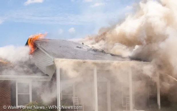 Fire emerges from the gable end of the roof as the main roof fire is attacked with water.