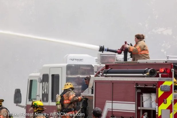 Youngsville firefighter Barrett controls the water canon to hit the roof fire.