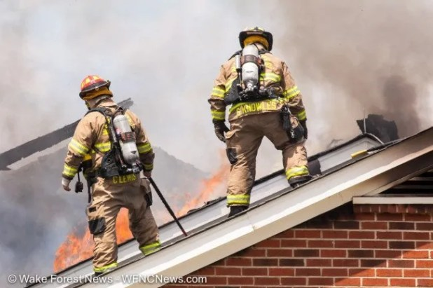 Wake Forest Fire Department Captain Lewis and Firefighter Knowles stand on the roof of the home and prepare to attack burning area.