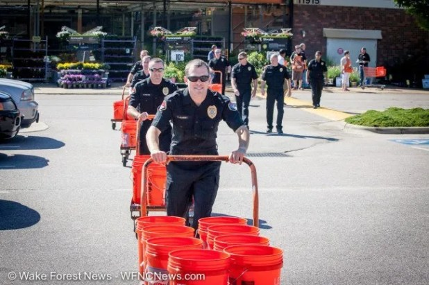 Wake Forest Police Department Officer Albert leads the train of orange buckets, ice, water, and officers to the challenge location.