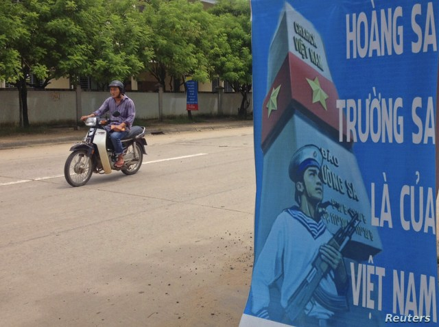 A man rides a motorcycle past a poster promoting Vietnam' sovereignty in the East Sea of the South China Sea, on Phu Quoc island, Sept. 11, 2014.