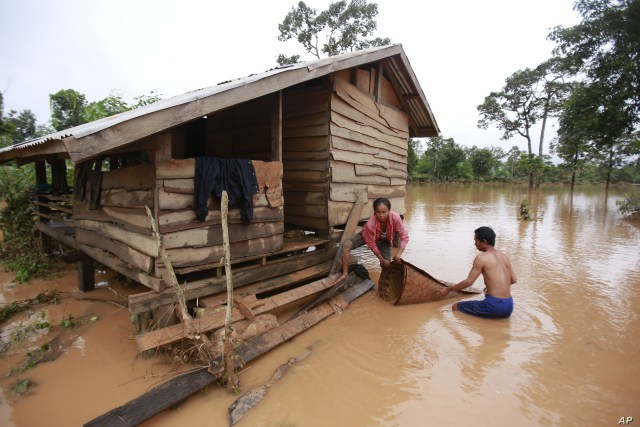 FILE - Kongvilay Inthavong and his wife, Thongla, clean up their house as the floodwaters start to recede in Sanamxay district, Attapeu province, Laos, July 26, 2018.