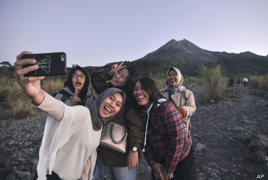 Local tourists take a selfie with the background of Mount Merapi, in Yogyakarta, Indonesia, Aug. 6, 2019. Yogyakarta and its hinterland are packed with tourist attractions, including Buddhist and Hindu temples of World Heritage.