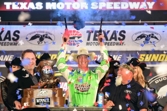 FORT WORTH, TEXAS - APRIL 09:  Kyle Busch, driver of the #18 Interstate Batteries Toyota, celebrates in Victory Lane after winning the NASCAR Sprint Cup Series Duck Commander 500 as Texas Motor Speedway President Eddie Gossage (L) and John Godwin of Duck Commander (R) look on at Texas Motor Speedway on April 9, 2016 in Fort Worth, Texas.  (Photo by Jared C. Tilton/NASCAR via Getty Images)