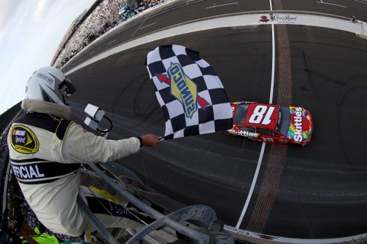 INDIANAPOLIS, IN - JULY 24:  Kyle Busch, driver of the #18 Skittles Toyota, takes the checkered flag to win the NASCAR Sprint Cup Series Crown Royal Presents the Combat Wounded Coalition 400 at Indianapolis Motor Speedway on July 24, 2016 in Indianapolis, Indiana.  (Photo by Sean Gardner/NASCAR via Getty Images)