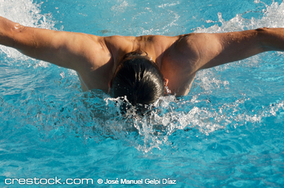 photo of a swimmer doing spring in swimming pool