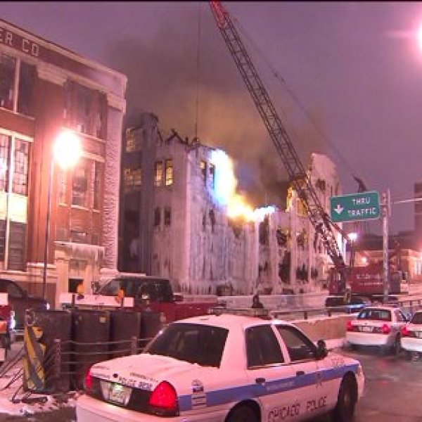 Demolition of warehouse underway, flames continue to burn