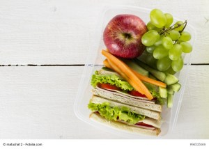 Lunchbox with sandwich, vegetables, fruit on white background.