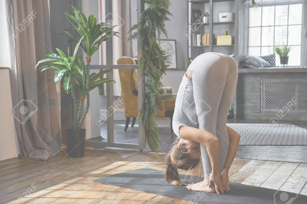Modern Woman Practicing Advanced Yoga In The Living Room At Home A Stock Regarding Beautiful Living Room Yoga Ideas House Generation