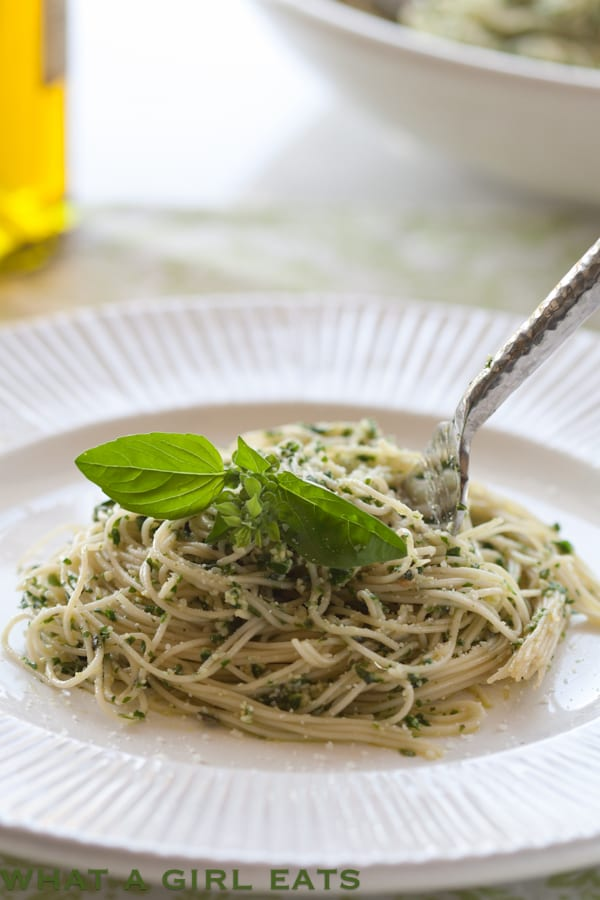 Fresh homemade basil pesto over angel hair pasta. Get the recipe on WhatAGirlEats.com