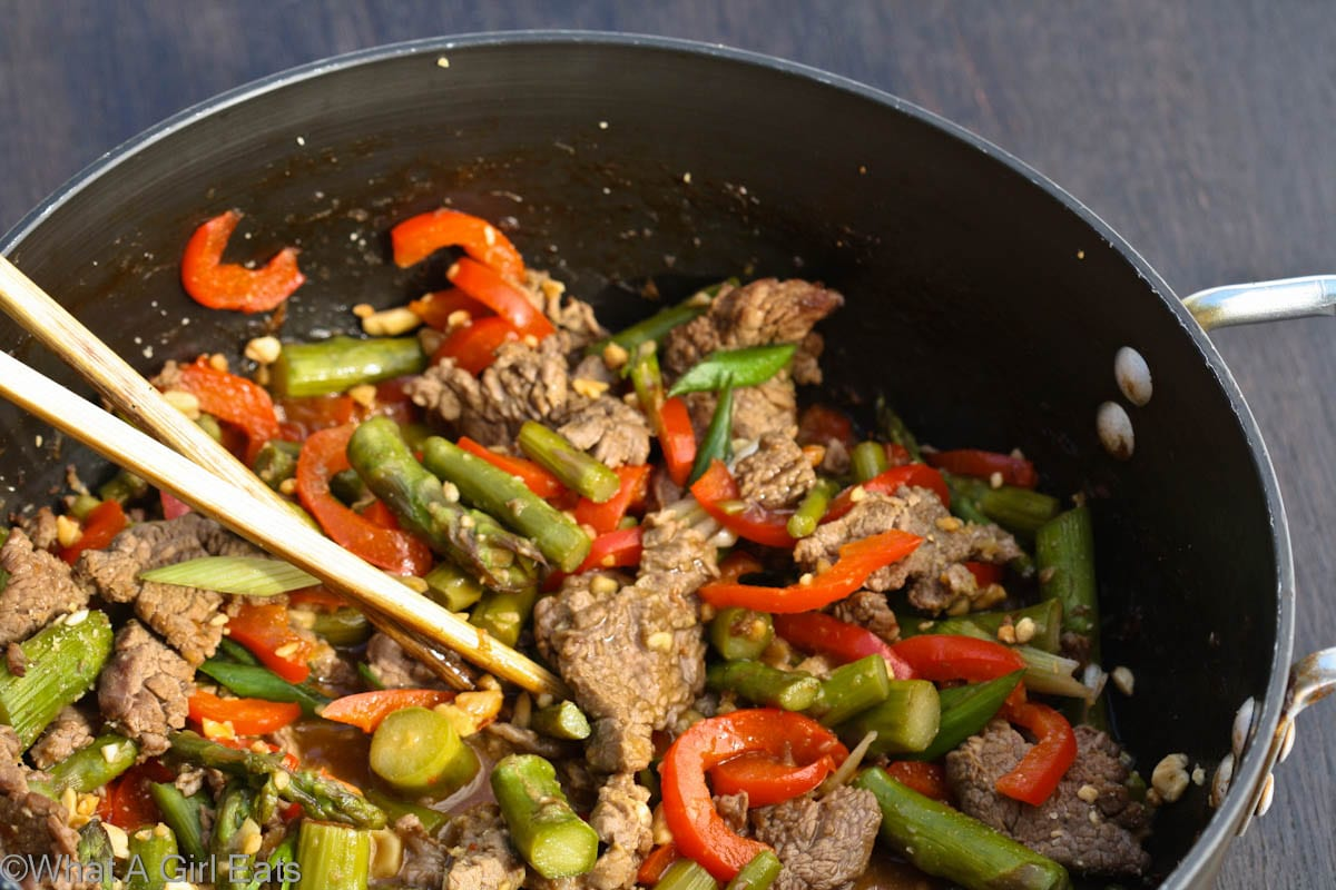 Szechuan beef is a popular, spicy Asian entree that's quick and easy to make. This recipe version is accented with sweet bell peppers and fresh asparagus. | Recipe from @whatagirleats