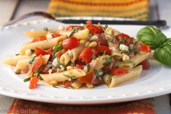 Summer pasta salad, full of salty prosciutto, gorgonzola cheese, garden tomatoes, pine nuts, and fresh basil. Served over tender pasta, this is an easy and delicious weeknight meal! | What a Girl Eats