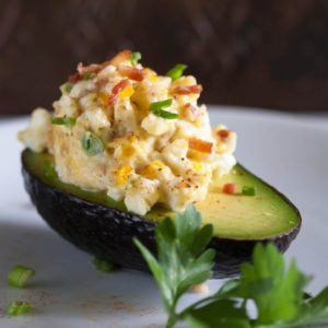 Egg salad with bacon is a delicious spin on a traditional egg salad recipe. Creamy egg salad and crisp bacon, combined and served in fresh avocado halves. | @whatagirleats