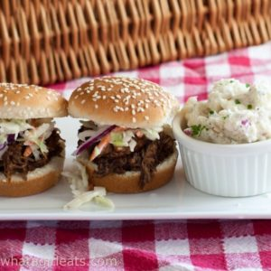Slow Cooker Pulled Pork Sliders - the perfect game day food, topped with homemade barbecue sauce! Recipe from What a Girl Eats.