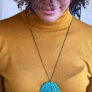 Turquoise medallion necklace handmade by families in Delhi. Modeled by my niece, Ana Sophia.