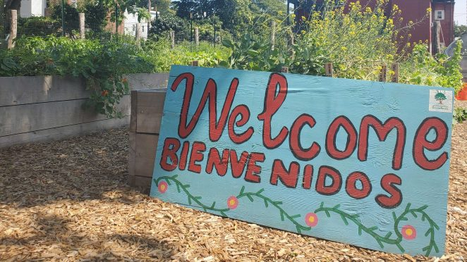 """A sign resting on a wooden garden bed overflowing with green plants reads """"Welcome, Bienvenidos."""""""