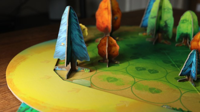"""A photo of the game Photosynthesis shows tree-shaped game pieces """"shading out"""" other trees on the board."""