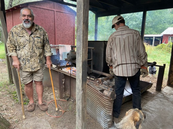 An older man with a gray beard stands on the right, smiling at the camera. He is wearing a camo shirt and khaki shorts and each hand has a walking stake. On the right, the back of a man in a striped shirt can be seen working on a wild rice processing bin. A dog can be seen in the lower right hand corner.