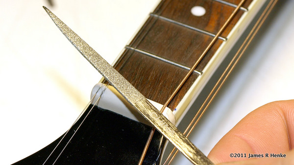 Using a small diamond file to deepen the new nut slots