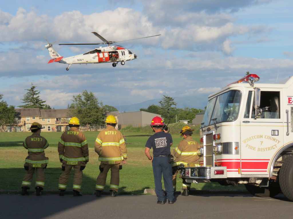 WCFD7 personnel watch as NAS Whidbey Island S&R crews simulate a rescue via helicopter (June 12, 2017). Photo: Discover Ferndale