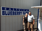 david and leah hughes pose by the eastview blueberry farm fruit stand 2018-07-25