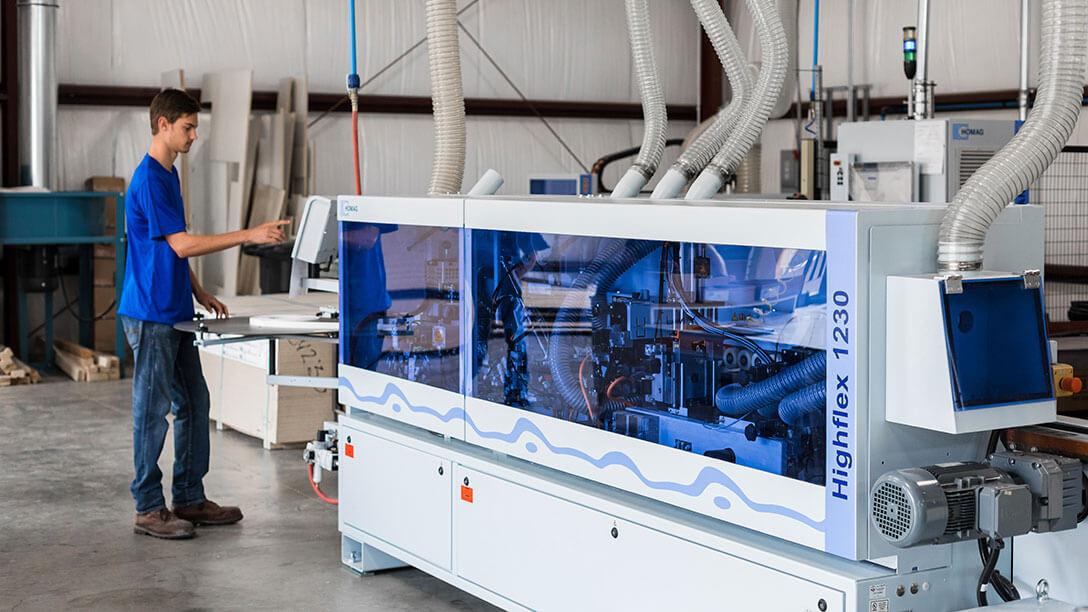 HighCraft employee operates edgebanding machinery