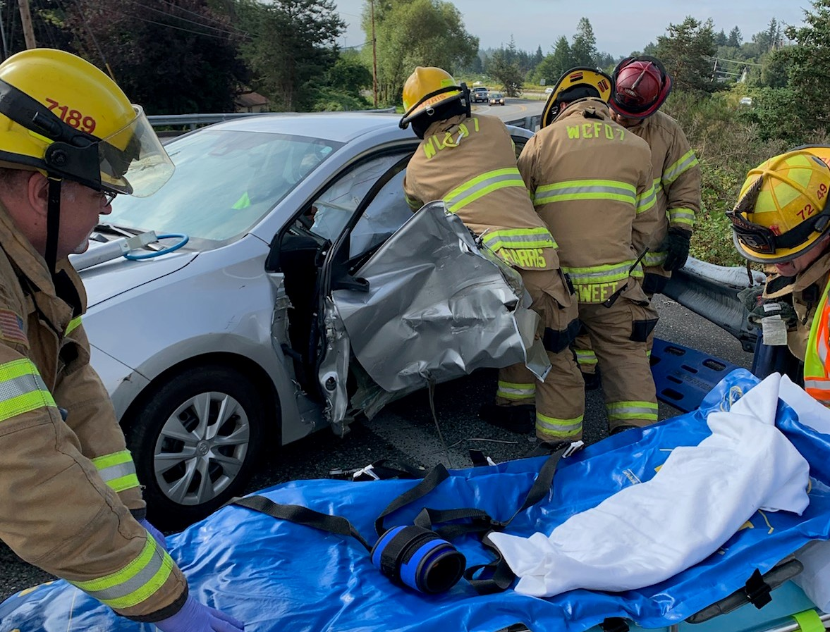 WCFD7 firefighters work to extricate a driver at the scene of a 2-vehicle crash at Pacific Highway and W Smith Road (August 16, 2019). Photo courtesy of WCFD7