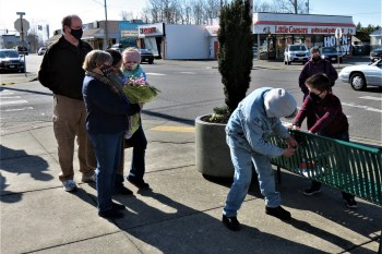 Chief Michael Knapp's family looks on as his grandson assists with the installation of a plaque on a bench dedicated in Knapp's memory. (February 26, 2021). Photo: My Ferndale News