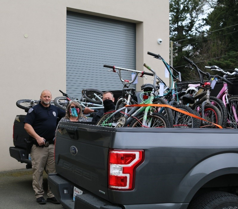 Ferndale Police Officer Eric Grant, Supervisor Kim Martin and Lieutenant Matt Huffman pose outside the Ferndale Police Station with bikes loaded to be donated. Photo: City of Ferndale
