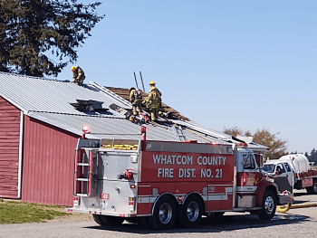 Firefighters removing roofing on a structure after extinguishing an interior fire (April 16, 2021). Photo: Whatcom News