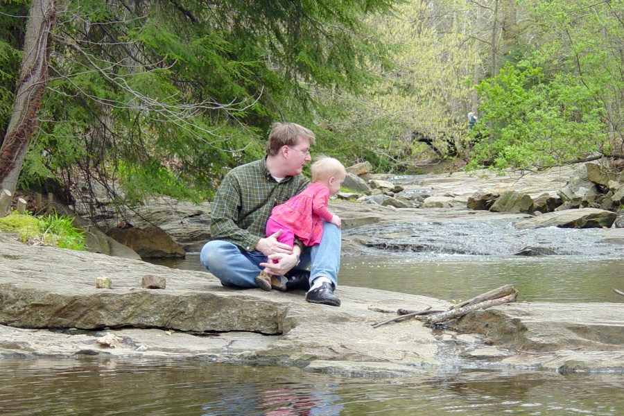 father and daughter by stream