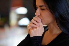close up of unhappy woman praying god at funeral