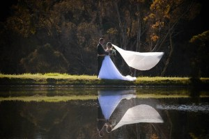 Bride and groom reflection in the lake with veil blowing in the wind at Clover Cottage Retreat, Manjimup