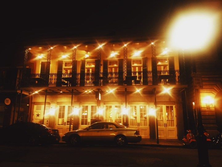 A two story building in the evening with its lights on.