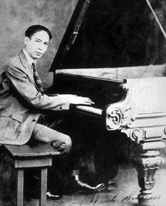 Jelly Roll Morton sitting at the piano.