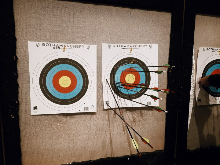 two archery targets; one target is blank and the other is full of eight bows because the shooter kept missing and landing on her husband's target at Gotham Archery