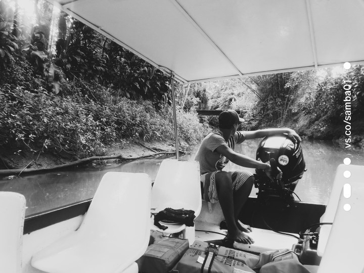 A young man in a black and white photo operates an engine for the monkey boat tour in Costa Rica.